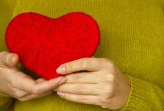 Plan rapproché sur le coeur rouge fait à partir de la laine disponible de la femme Image libre de droits