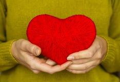 Plan rapproché sur le coeur rouge fait à partir de la laine disponible de la femme Image stock