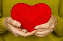Plan rapproché sur le coeur rouge fait à partir de la laine disponible de la femme Photographie stock libre de droits