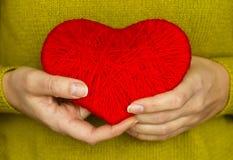 Plan rapproché sur le coeur rouge fait à partir de la laine disponible de la femme Images stock