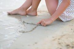 Plan rapproché sur le dessin de jeune femme sur le sable Image stock