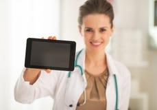 Plan rapproché sur le docteur montrant à PC de comprimé l'écran vide Photo stock