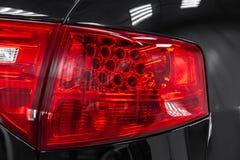 Plan rapproché sur le feu de freinage arrière de LED de couleur rouge sur une voiture noire derrière un suv après nettoyage image stock