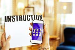 Plan rapproché sur le livre d'instruction et le smartphone à disposition de la femme au foyer photographie stock libre de droits