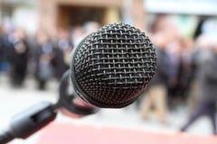Plan rapproché sur le microphone et la foule brouillés derrière Images libres de droits