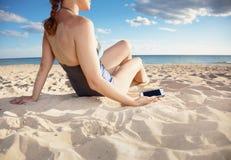 Plan rapproché sur le smartphone à disposition de la femme sur la plage sur le bord de la mer photo stock