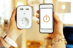Plan rapproché sur le smartphone avec l'appli à la maison futé dans des mains de femme images libres de droits