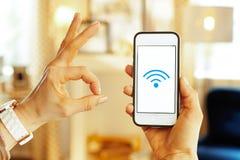 Plan rapproché sur le smartphone avec le signal fort de wifi à disposition de la femme images stock