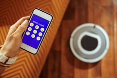 Plan rapproché sur le smartphone dans le vide femelle de main et de robot sur le plancher images libres de droits