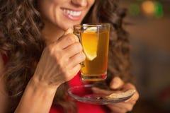 Plan rapproché sur le thé potable de gingembre de jeune femme heureuse avec le citron Photographie stock libre de droits