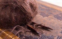 Plan rapproché sur les aiguilles de tricotage en bois, qui sont entourées par le fil pelucheux pour le tricotage et le mensonge s images libres de droits