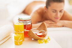 Plan rapproché sur les ingrédients et la femme de thérapie de station thermale de miel à l'arrière-plan Images stock