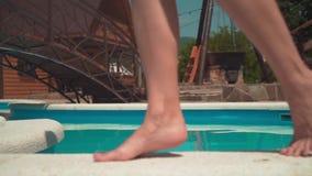 Plan rapproché sur les jambes d'une femme comme elle avance sur la pointe des pieds le long du bord de la piscine banque de vidéos