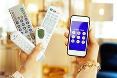 Plan rapproché sur les télécommandes et le smartphone avec l'appli à la maison futé photo libre de droits