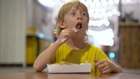 Plan rapproché tiré d'un petit garçon mangeant une gaufre savoureuse dans un café de rue Concept de nourriture de rue banque de vidéos