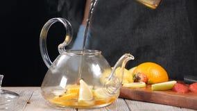 Plan rapproché tiré de l'eau bouillie étant versée dans le fruit de wuth de théière Concept de brassage de thé Mouvement lent L'e banque de vidéos