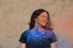 Plan rapproché tiré de la femme heureuse de brune avec de longs cheveux bouclés couverts de peinture sèche colorée Holi au désert photos stock