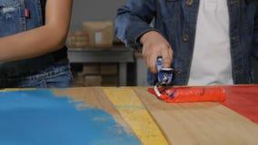 Plan rapproché tiré des conseils de peinture de garçon et de fille avec des rouleaux dans le mouvement lent Peu badine jouer des  banque de vidéos