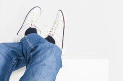 Plan rapproché tiré des jambes des hommes sur la La blanche d'espadrilles et de jeans de mode Photos libres de droits