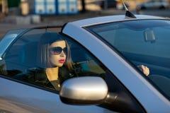 Plan rapproché tiré du joli modèle de brune avec les lèvres rouges utilisant des lunettes de soleil conduisant un cabriolet L'esp photos stock