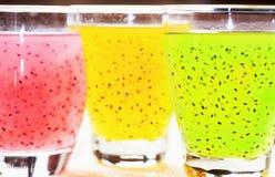 Plan rapproché trois verres avec la boisson de fruit /pink, jaune, vert avec des graines de basilic Images libres de droits