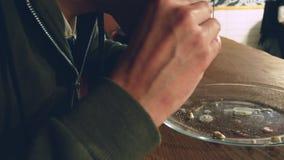 Plan rapproché Un homme mange un hamburger Le processus de manger les hamburgers délicieux banque de vidéos