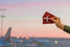 Plan rapproché un jouet et passeports de modèle d'avion fenêtre de fond d'aéroport à la grande à l'aube Photo libre de droits