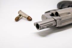 Plan rapproché un pistolet avec des balles d'isolement sur le fond blanc Photo libre de droits
