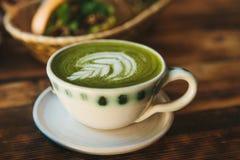 Plan rapproché Une tasse de thé vert a appelé le thé de Matcha ou le café de vert avec un modèle Photographie stock