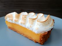 Plan rapproché une tranche de tarte Mouthwatering de meringue de citron d'un plat bleu photographie stock