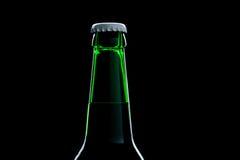 Plan rapproché vert de bière de bouteille au-dessus de noir Photographie stock