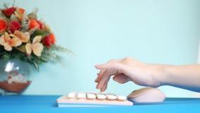 Plan rapproch? carte vid?o de salutation ?l?gante les mains femelles dactylographient sur un clavier rose, ? c?t? d'une fleur Sur photographie stock