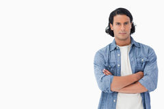 Plan rapproché d'un homme brun de cheveu croisant ses bras Image stock