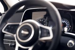 Plan rapproch? d'un tableau de bord moderne dans une voiture ch?re Le volant est brouill? images libres de droits