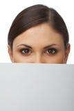 Plan rapproché d'une femme se cachant derrière le panneau-réclame Photographie stock libre de droits