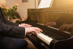 Plan rapproché d'une main du ` s d'interprète de musique jouant le piano Photographie stock libre de droits