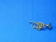 Plan rapproch? d'une trompette miniature sur le fond bleu images stock