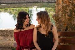 Plan rapproch? de deux amis s'asseyant sur un banc par un lac, photo stock