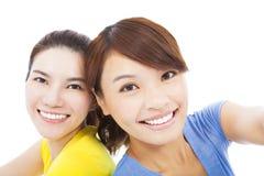 Plan rapproché de deux jeunes filles heureuses au-dessus de blanc Image libre de droits