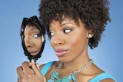 Plan rapproché de femme d'Afro-américain regardant elle-même dans le miroir au-dessus du fond coloré Photos stock