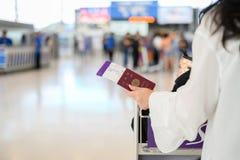 Plan rapproch? de fille tenant les passeports et la carte d'embarquement ? l'a?roport image stock