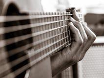Plan rapproché de jouer une guitare acoustique Photographie stock libre de droits