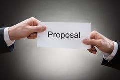 Plan rapproché de la main de deux hommes d'affaires tenant le papier de proposition Photographie stock libre de droits