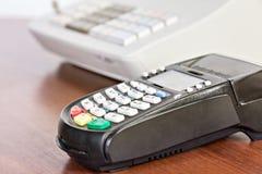 Plan rapproché de lecteur de carte de crédit sur le fond de caisse enregistreuse Photographie stock libre de droits