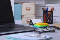 Plan rapproch? de lieu de travail confortable dans le bureau avec l'ordinateur portable, la souris, le carnet, les verres, le sty photo stock