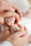 Plan rapproché de main de chéri dans des mains de parents Concept de la famille Photographie stock libre de droits