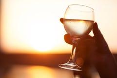 Plan rapproché de main tenant le verre de la boisson Photos stock