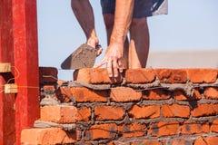 Plan rapproché de truelle de brique d'artisan de bâtiment Images stock