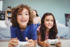 Plan rapproché des enfants de mêmes parents heureux avec des contrôleurs jouant le jeu vidéo Photos libres de droits