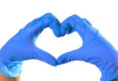 Plan rapproch? des mains dans les gants verts de latex Le coeur est pli? des mains images libres de droits